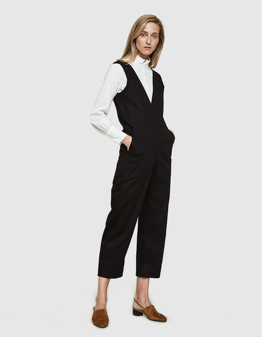 2f2dfcdec8a Tailored jumpsuit from Toit Volant in Black. Thick straps. Deep V-neckline.  Concealed back zip closure. Front and back patch pockets. Slim straight leg.