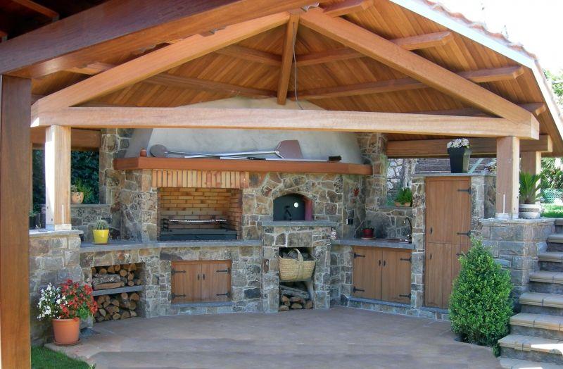 Cocina exterior con tejado a dos aguas en vigas de madera for Tejados de madera para exterior