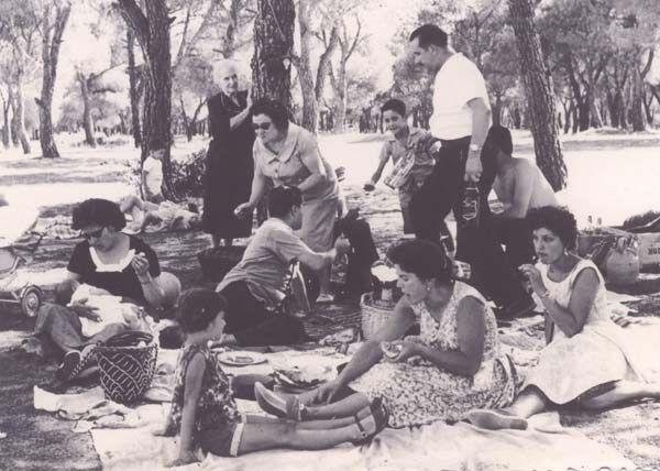 Día de campo en la Casa de Campo (Madrid)comiendo la tortilla. 1962. No falta detalle: el botijo, la cazuela, la botella de gaseosa, la frasca del vino.