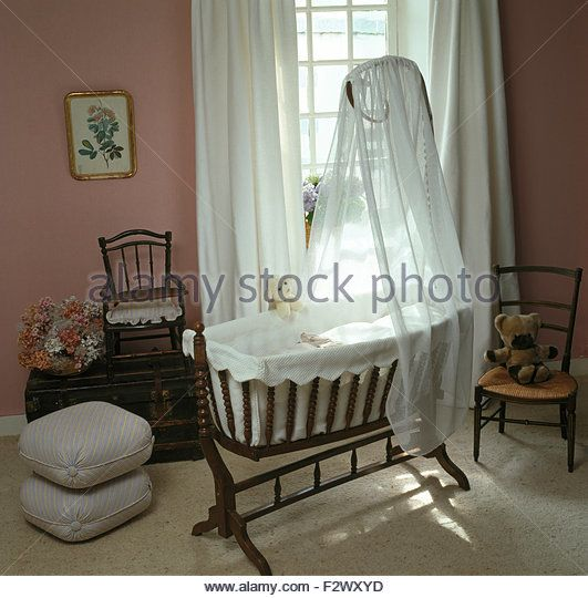 White voile drapes on a Victorian style rocking cradle in eighties nursery bedroom - Stock Image