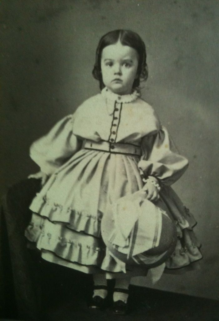 Young girl wearing dress with hoop. American.