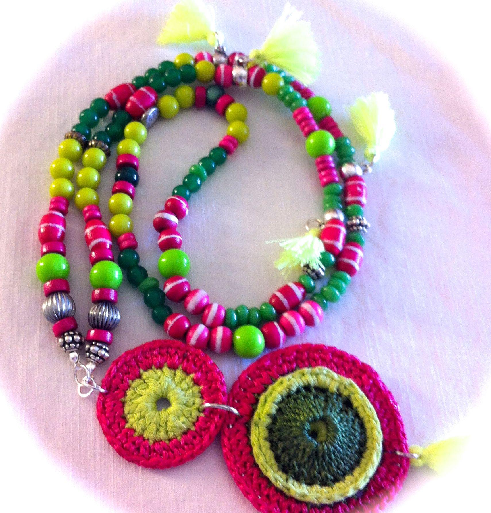 Collar XL, con 3 rosetones superpuestos y uno añadido en tres colores, tira de cristales verdes, bolitas de madera fucsia, piezas variadas en resina, piezas de metal y de resinas intercaladas con 5 pompones de algodón en neón 23€