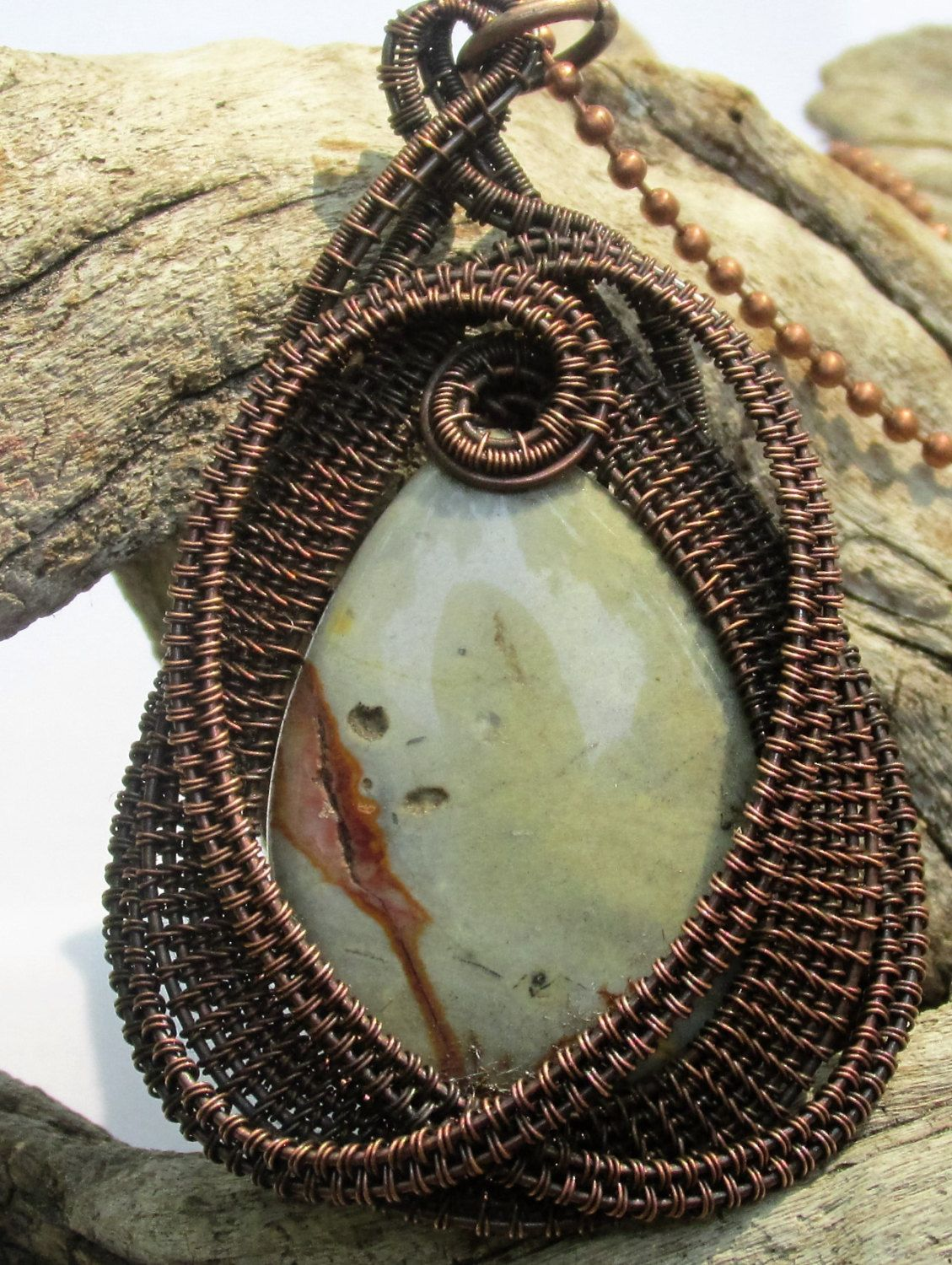 A handmade wire wrapped necklace, copper wire woven around polished ...