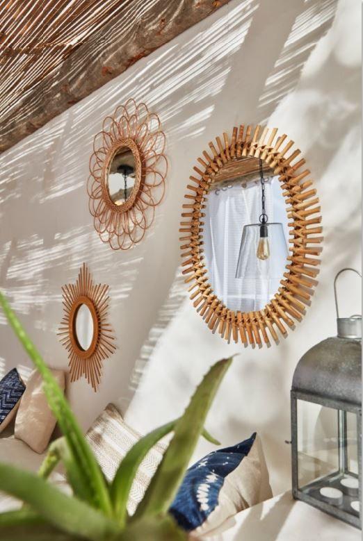 Une Collection De Miroirs En Rotin Habille Le Mur En Beton Cire Blanc De Ce Patio D Inspiration Mediterraneenne Miroir En Rotin Decoration Deco Mur Exterieur