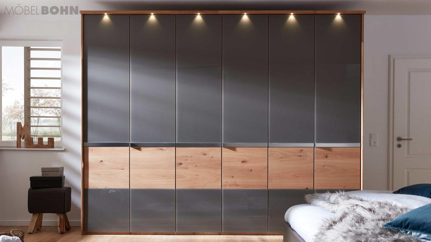 Der praktische Drehtürenschrank 530 mit dem beleuchteten Passpartout 973 hat Maße von ca. 306 x 240 x 58 cm (BxHxT) und weist auf dem Korpus aus Balkeneiche-Nachbildung sechs Türen mit havannafarbener Glasfront und eine Bauchbinde im harmonisch abgestimmten Balkeneichenholz auf. #meinbohn #Schlafzimmer #Stuhl #Tisch #Bett #black #wood #sleepingroom #style #stylisch #stilvoll #premium #quality #qualität #hot #new #interliving
