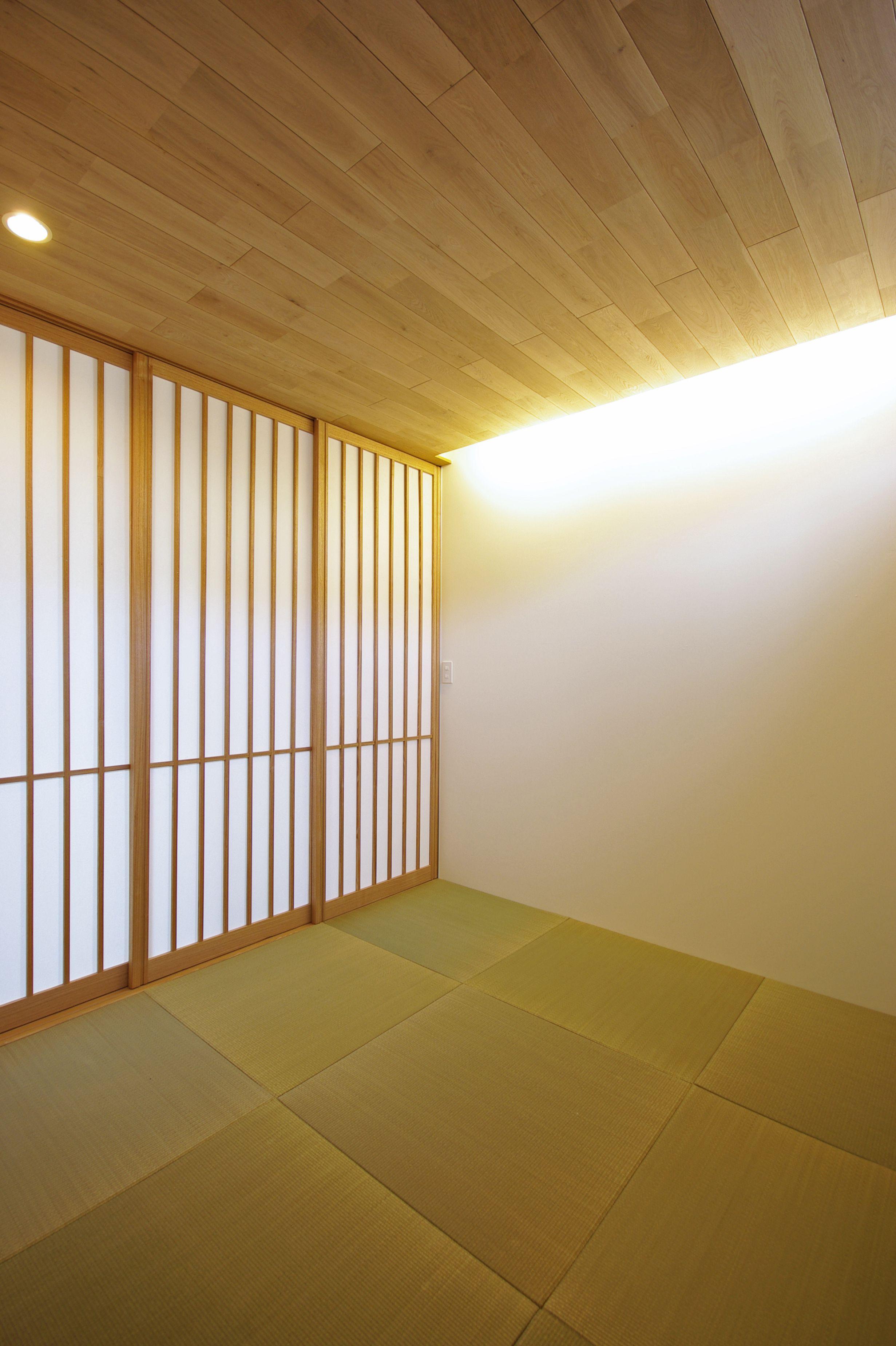 豊岡の家 トヨオカノイエ 玄関横の和室 土間から入る 少し変わった配置の客間です 縁無半帖畳と間接照明で現代風に 板張りの天井と障子戸で落ち着く空間に 天井板はナラ材です 和室 和室照明 間接照明 障子 縁無畳 半帖畳 イグサ ナラ ナラ材