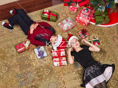 brother and sister lying on floor. - Brother and sister lying on floor near christmas tree, Model: Shania Chapman - Agent is Breann at MMG. breann@nymmg.com and Josh Chapman