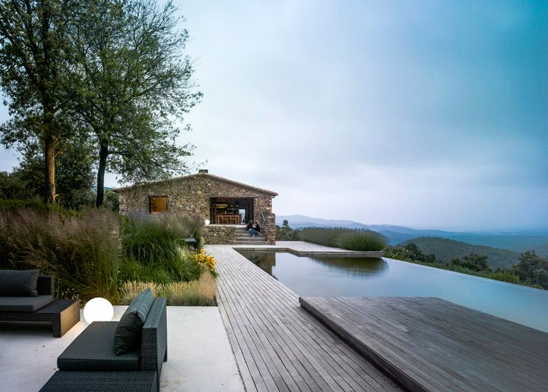 Rusted steel frames project from the traditional stone and plaster - Residence Vacances Ardeche Avec Piscine