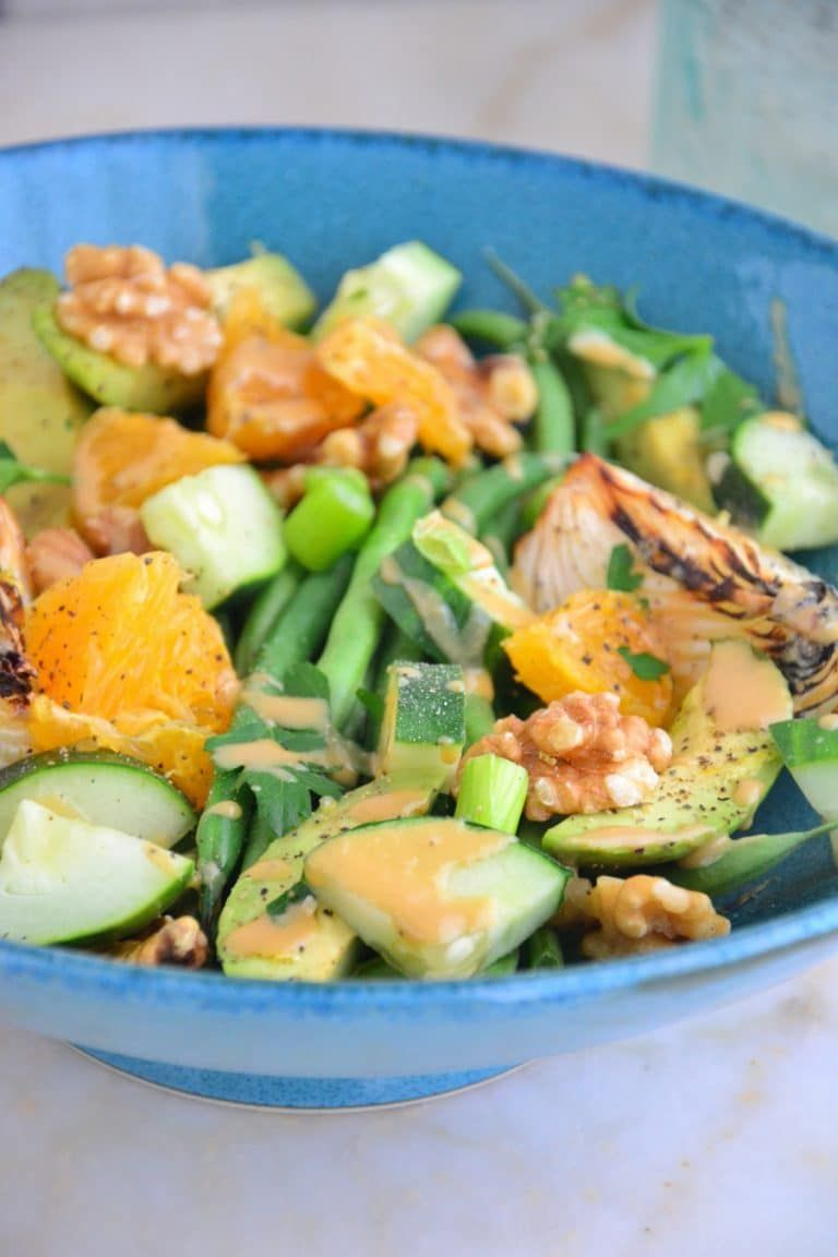 This French Green Bean Salad is gorgeous and loaded with nutrients and fresh vegetables and fruits like cucumbers and oranges in a lovely blue bowl.