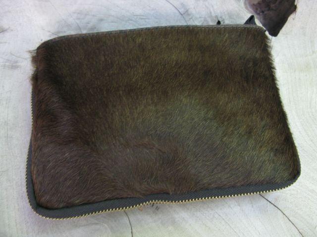 Bolso en potro en la parte frontal de 22 cm ancho por 15 cm alto. Cremallera interior y asa larga.