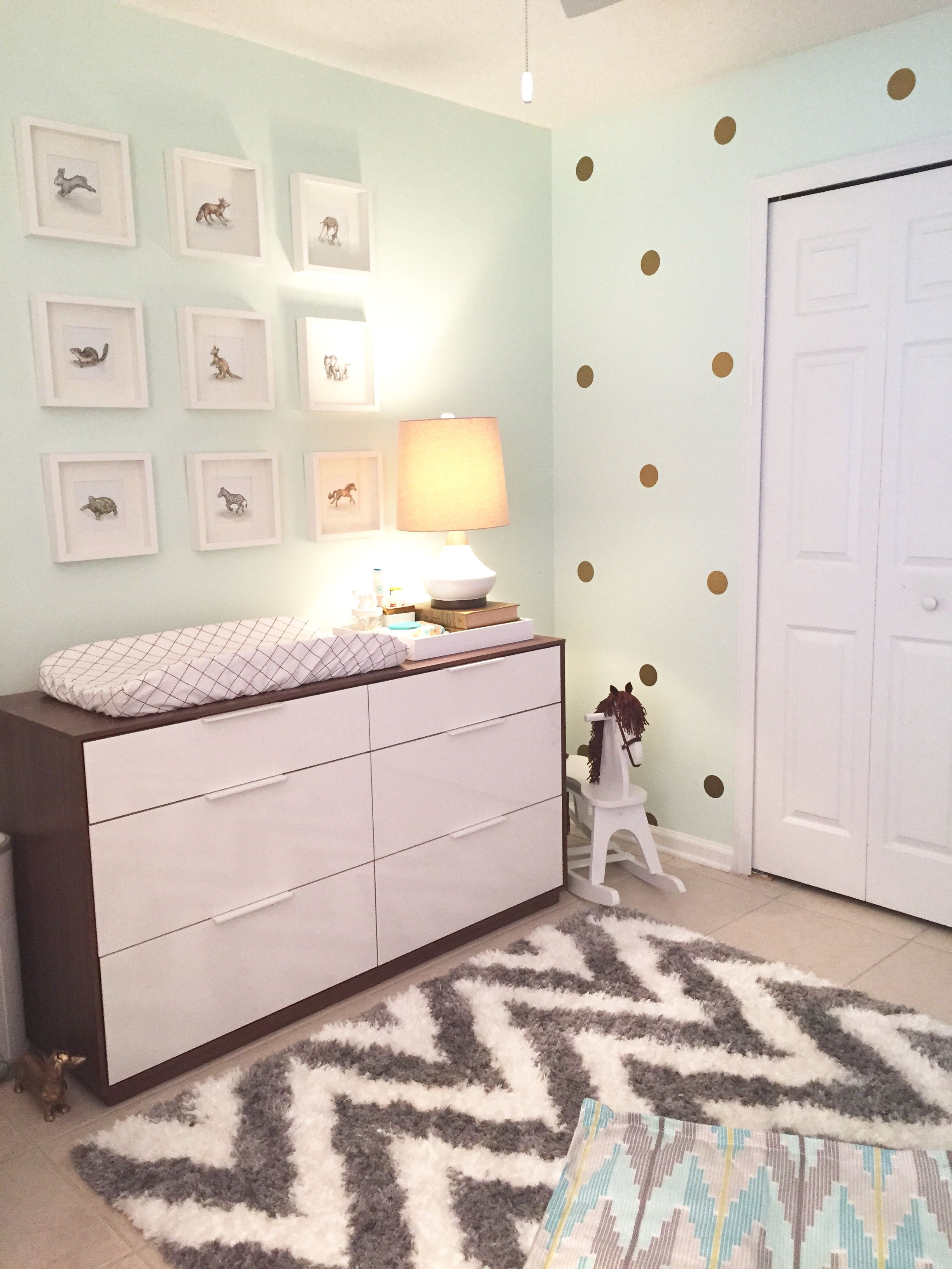 A modern gender neutral nursery featuring mint walls with gray and gold accents.