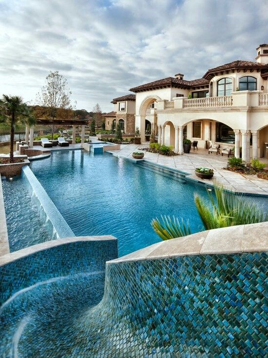 A gorgeous slide built into this massive pool! This looks like a great back  yard