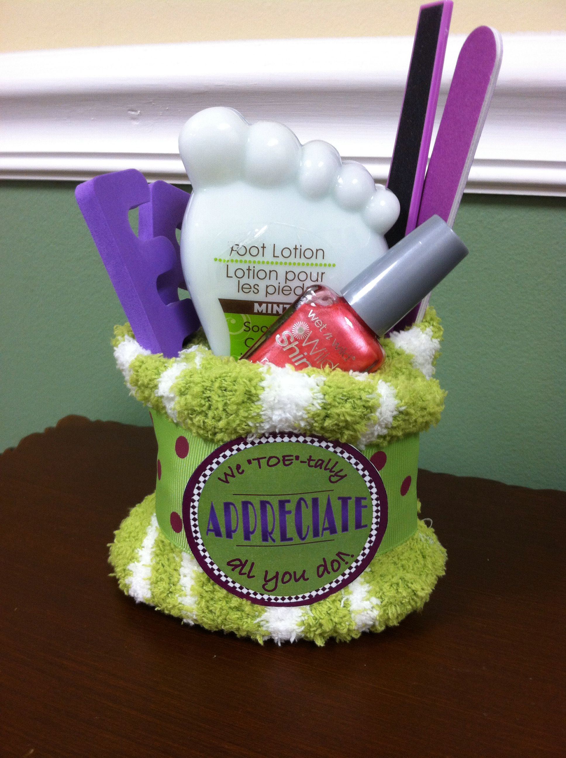 """""""We TOE-tally appreciate all you do!"""" Made 15 of these for volunteer appreciation gifts but forgot to photograph them. Color scheme of others was much better, all shades of lime and plum. This was a leftover...included fuzzy socks, nail polish, foot scrub, pedicure kit items. Total $4 each."""