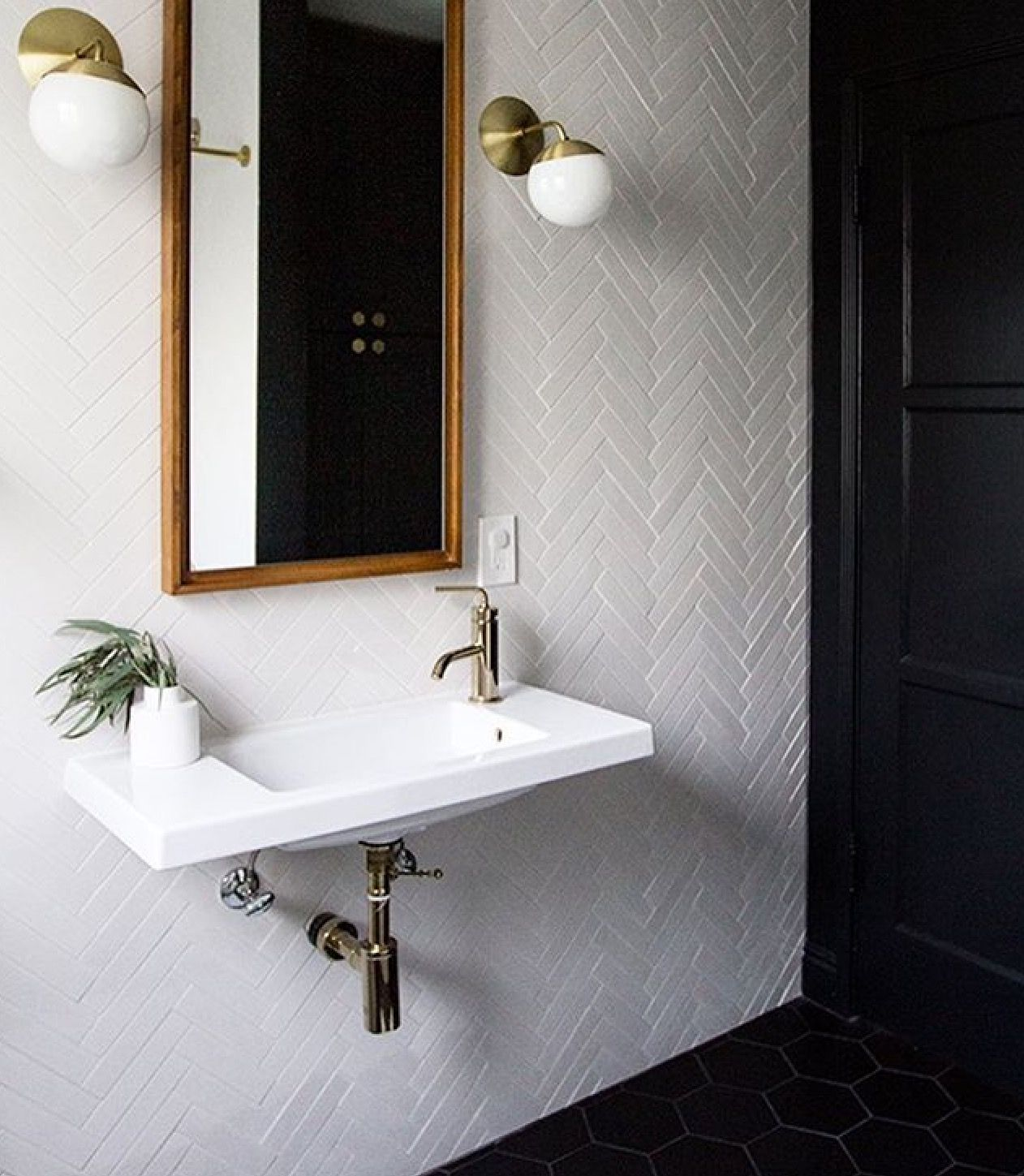 Herringbone home pinterest herringbone powder room and bath walls clad in a white herringbone tiles with a west elm floating wood wall mirror illuminated by cedar moss alto sconces over a white porcelain wall mount dailygadgetfo Choice Image