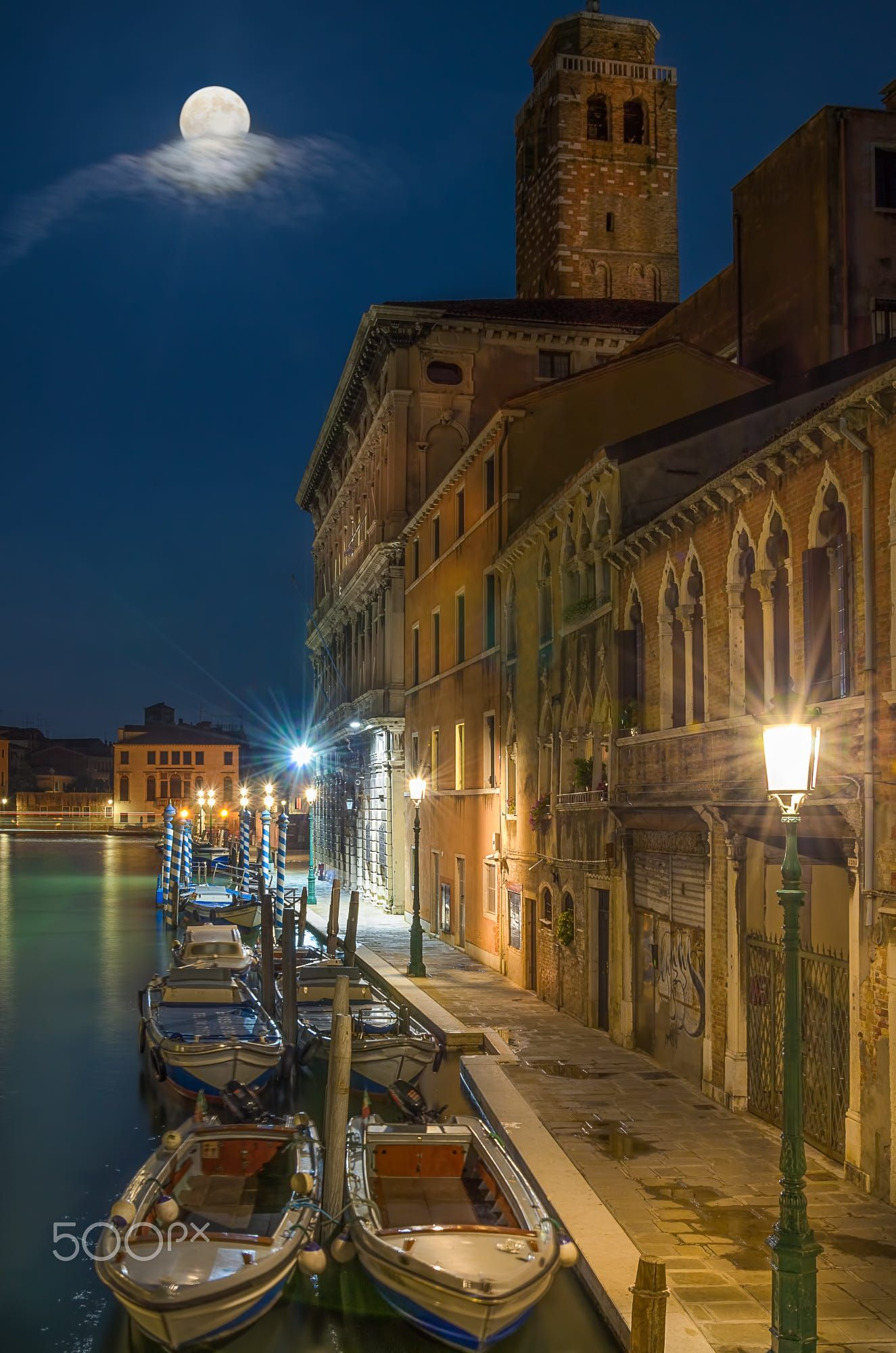 Anchored boats in Venice canal, street lit by lamps and full moon, with moving clouds and green water reflection.