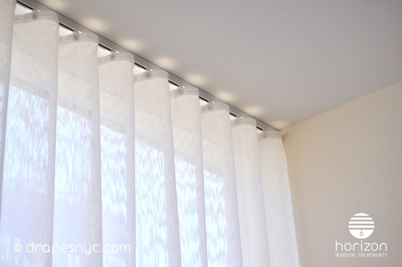 Sheer ripple fold curtain on a white curtain track Drapery