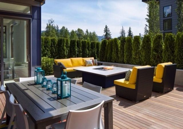 sonnendeck mit holzdielen verlegt moderne terrassenmbel gelbe auflagen feuerstelle im mittelpunkt - Moderne Dachterrasse Unterhaltungsmoglichkeiten