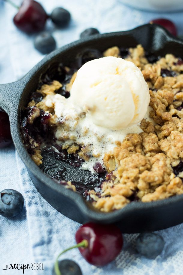 Berry Cherry Crisp: Fresh cherries and blueberries topped with an oatmeal cookie crumble and baked until golden and crunchy! The perfect summer dessert for all of that beautiful fruit! Perfect for topping with ice cream. www.thereciperebel.com