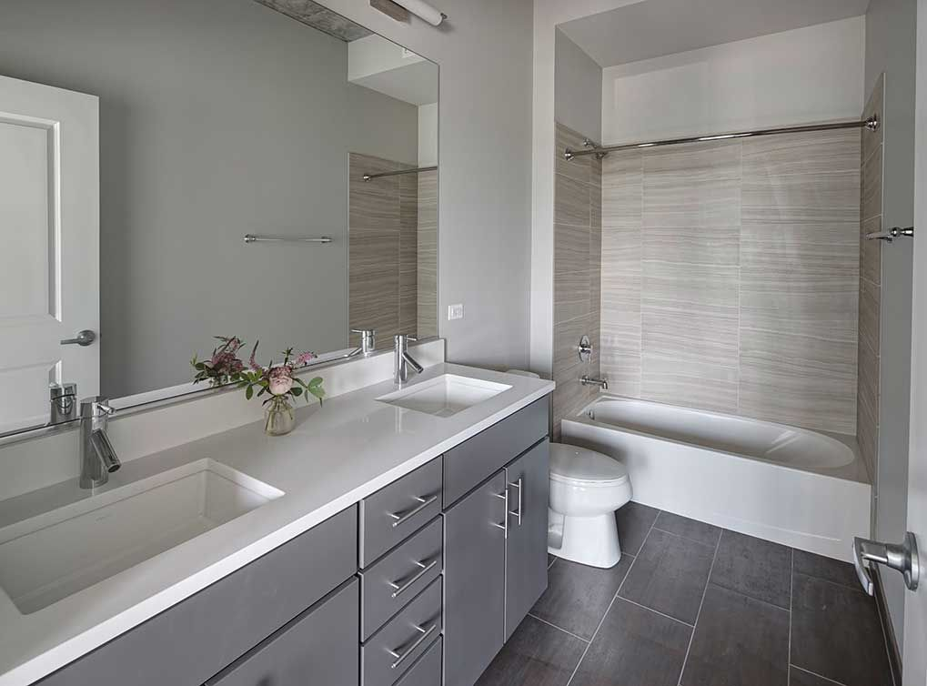 Beautiful model bathroom featuring gray cabinets ...