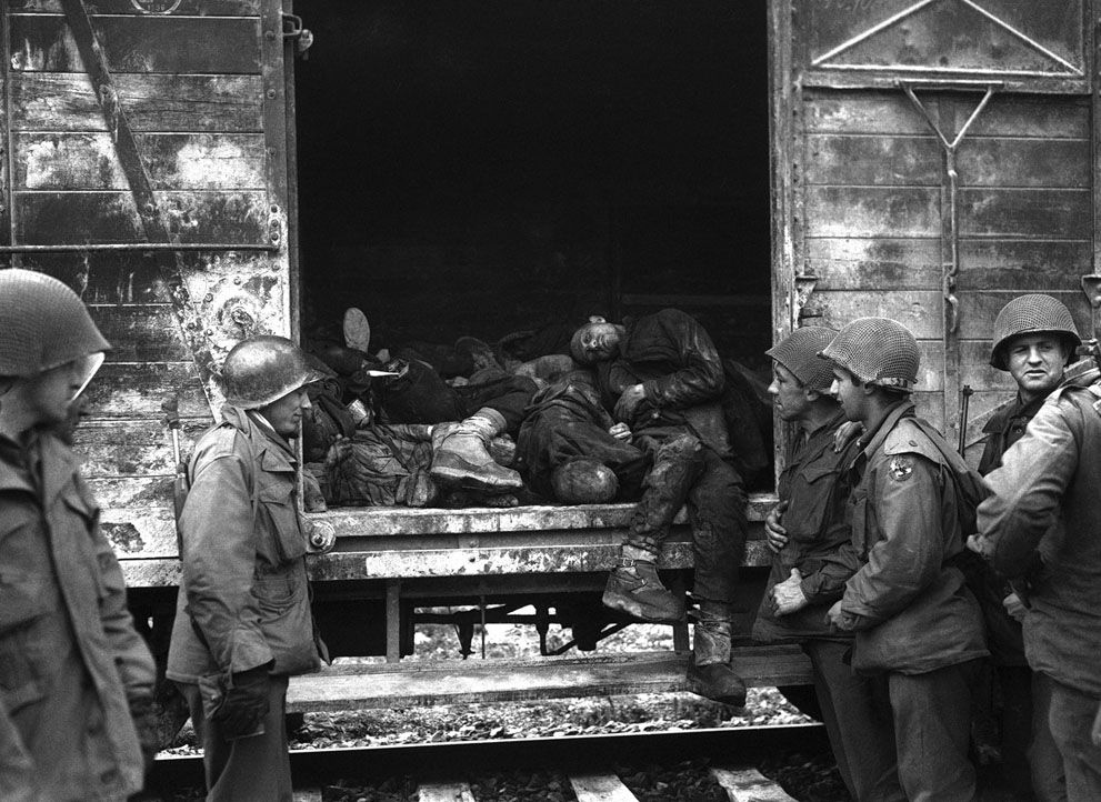 American soldiers silently inspect some of the rail trucks loaded with dead which were found on the rail siding at the Dachau concentration camp in Germany, on May 3, 1945. (AP Photo)