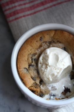 """Deep Dish Cookie Pie  The Blue-Eyed Bakers' Chocolate Chip Cookie dough (recipe follows) 6 small ramekins (about 4"""" diameter) Vanilla ice cream Preheat oven to 375F. Fill ramekins 3/4″ deep with raw, room temperature cookie dough.  Set ramekins on baking sheet and  bake on the middle rack of the oven for 13-16 minutes, or until the top is just slightly golden brown.  You're aiming for slightly undercooked cookies. Place ramekins on individual plates or napkins ..."""