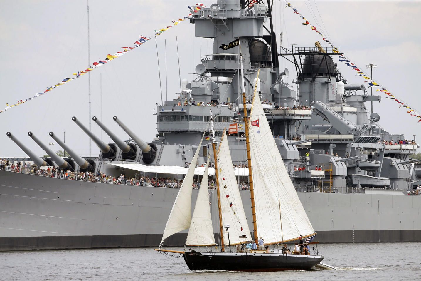 The schooner Hindu sails up the Delaware River between Camden, N.J. and Philadelphia past the USS New Jersey during a tall ships parade, Thursday, June 25, 2015. A tall ship festival is scheduled to be open to the public through Sunday, June 28. Organizers say the event on both sides of the river will allow people a close-up view of famed ships such as the French vessel L'Hermione, Brazilian vessel Cisne Branco, Canadian Barque Picton Castle, and Philadelphia's own Gazela.