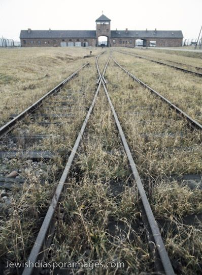 Photograph of railroad tracks and building inside of the Auschwitz II-Birkenau death camp in Oświęcim (Oswiecim), Poland. The camp's administration building surrounds the portal for the railroad trains carrying prisoners into the camp, where ¾ were gassed to death within hours of arrival. At least 1.1 million Jews, 75,000 Poles, and some 19,000 Roma (Gypsies) were killed Auschwitz and Birkenau complex, with some estimates to 3.5 million victims