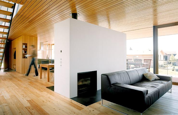 holzhaus mit gro en fensterfronten kamin als raumteiler. Black Bedroom Furniture Sets. Home Design Ideas
