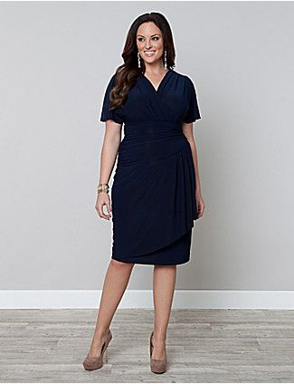 Haute and sultry, our Danika Draped Dress is a beautiful piece with an asymmetrical line at the bottom waist of a fully ruched torso. This becoming silhouette finishes with a faux wrap straight skirt for a slimming effect that includes gathering and a flounce in the front for flirty appeal. Dramatic dolman sleeves flow over the arms in a stylishly feminine way and the surplice neckline adds just the right amount of coverage. catherines.com