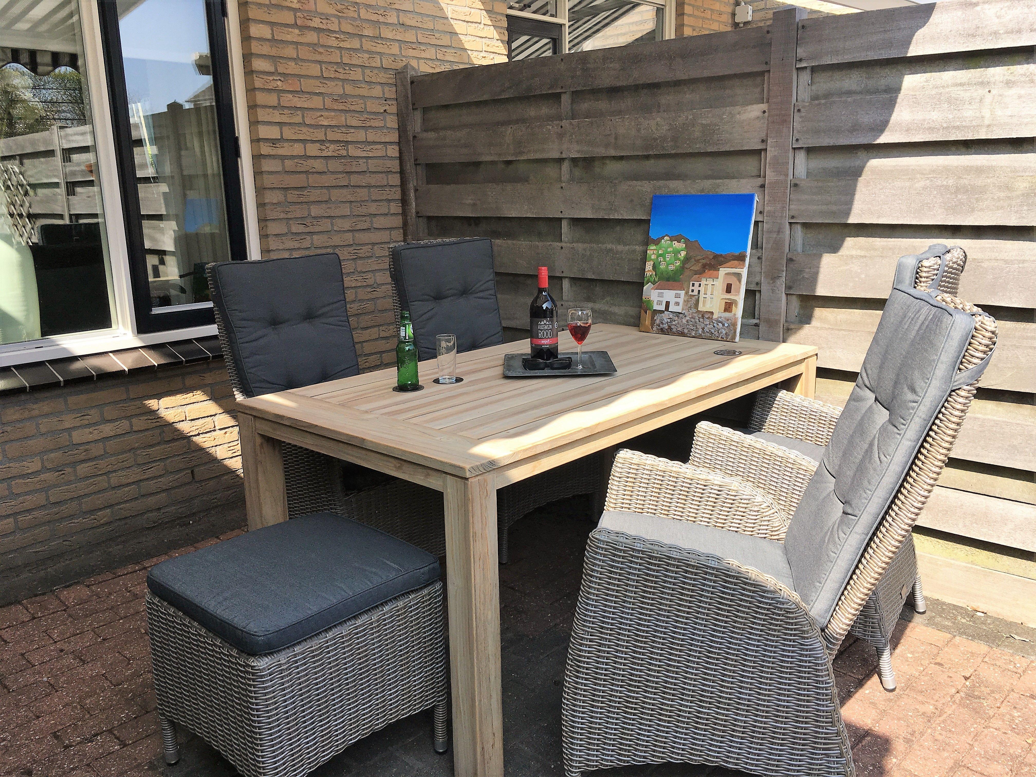 Tuinset met houten tafel en dining stoelen van vlechtwerk