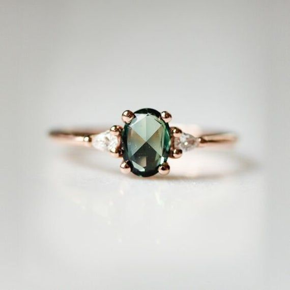 Green Sapphire Engagement Ring For those with wild, romantic hearts, we designed the Amelia Ring. A unique, rose cut dark green sapphire nestles between two petite diamonds, enveloped in secure 14k rose gold—a manifestation of hopeless romance. We love this ring for someone that wants something a