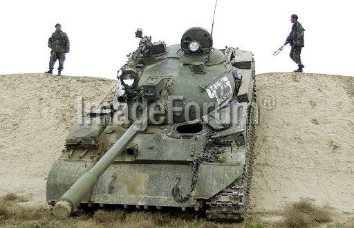 Two afghan soldiers stood guard behind a weapon cache (not in the picture) as a Russian-made T-55A tank is parked next to them during a campaign on collecting heavy weapons from regional commanders in the northern city of Mazar-i-Sharif, 02 December 2003.