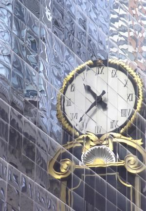 Reflection of a huge clock attached to a building in New York.
