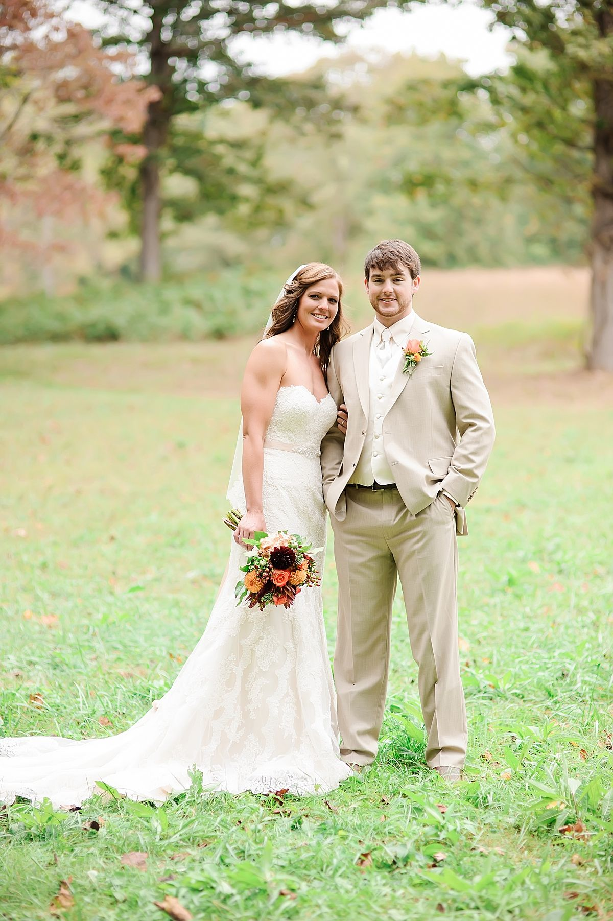 66d139492df Bride in strapless lace wedding dress with groom in light tan suit at  outdoor wedding in Knoxville