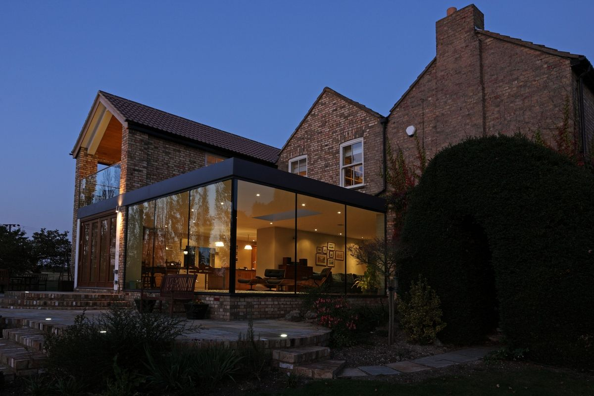 Modern glass addition to otherwise traditional home for Traditional house architecture