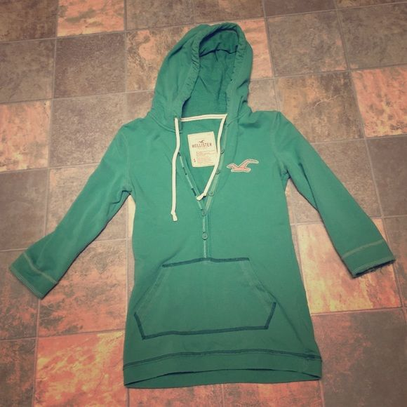Hollister green shirt Green Hollister light 3/4 arm length hoodie with buttons on the front and pocket. Has HCO written on the top of the hood. In very good condition minus the fringe on the sleeve. No holes, stains, or rips. From a pet and smoke free home. Hollister Tops