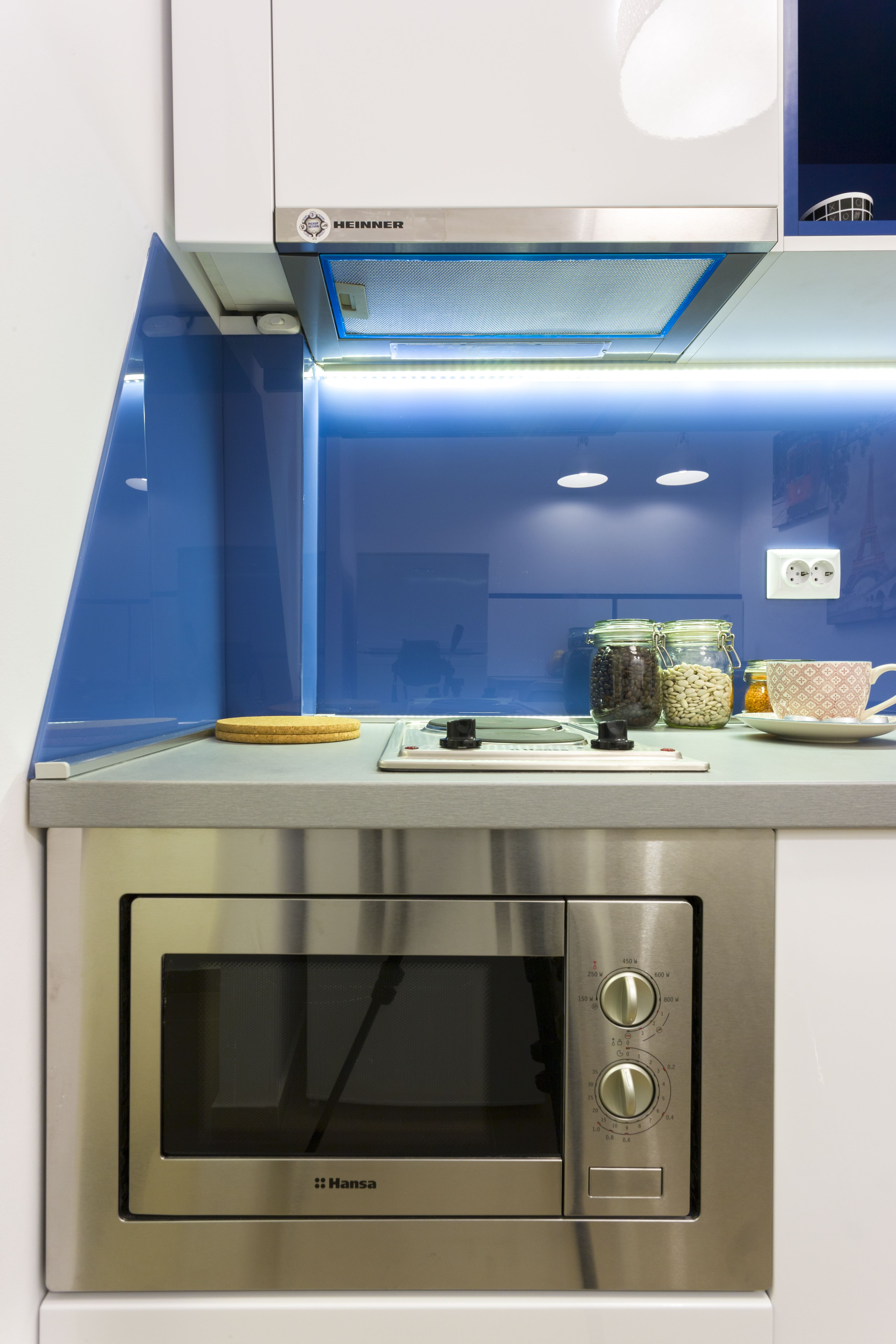 Small kitchen design with blue glass back wall and white furniture