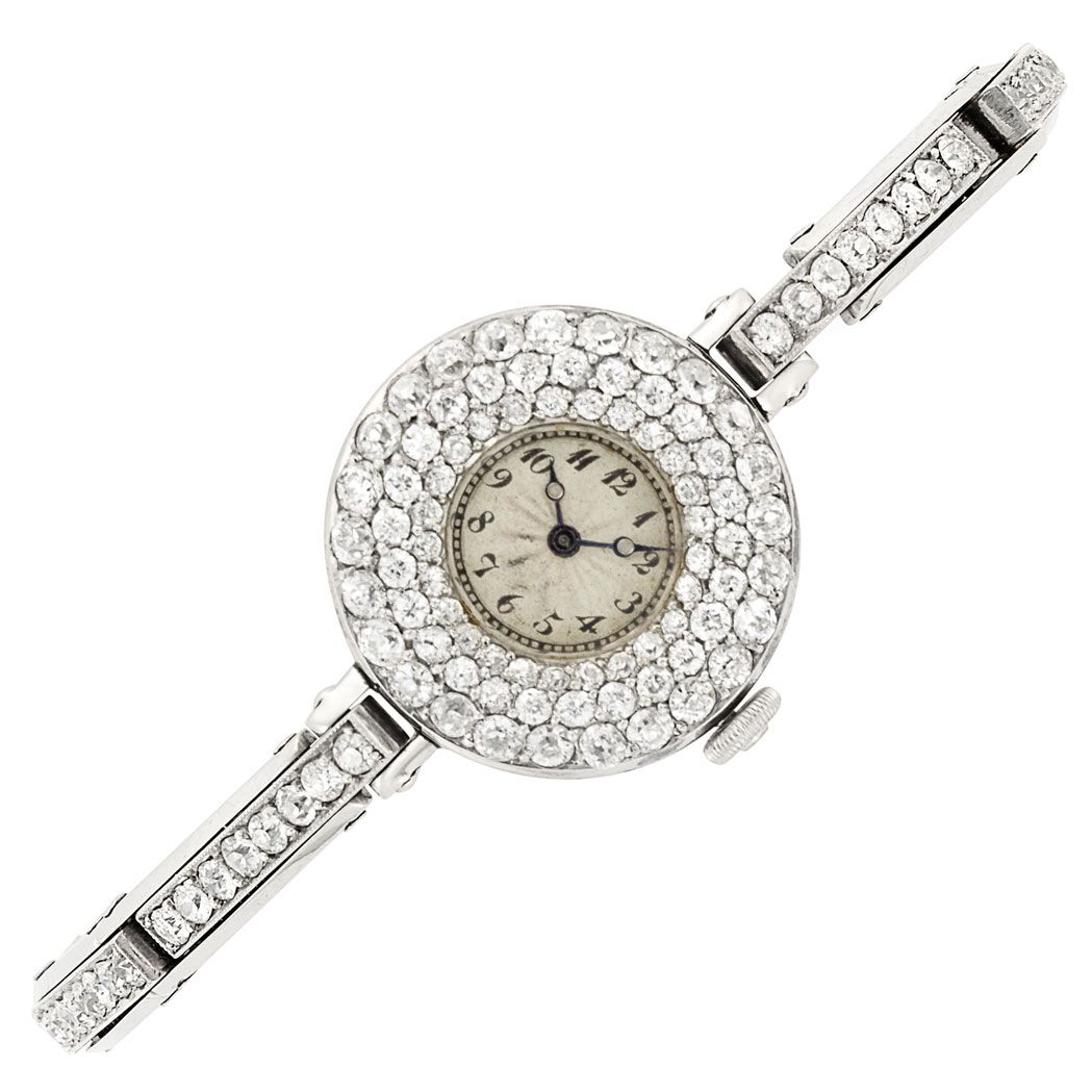 Platinum and Diamond Wristwatch, France, circa 1920 Mechanical, centering a circular off-white guilloche dial with black Arabic numerals, within a circular pave-set diamond case, completed by a diamond-set expandable bracelet, set throughout with 139 old European-cut diamonds approximately 3.75 cts., bracelet signed Brevetes. C.DG., case with French assay mark, movement unsigned, approximately 25.8 dwts. gross. Length 5 3/4 inches, adjustable.