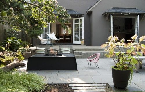 French doors to concrete patio that steps down Garden design