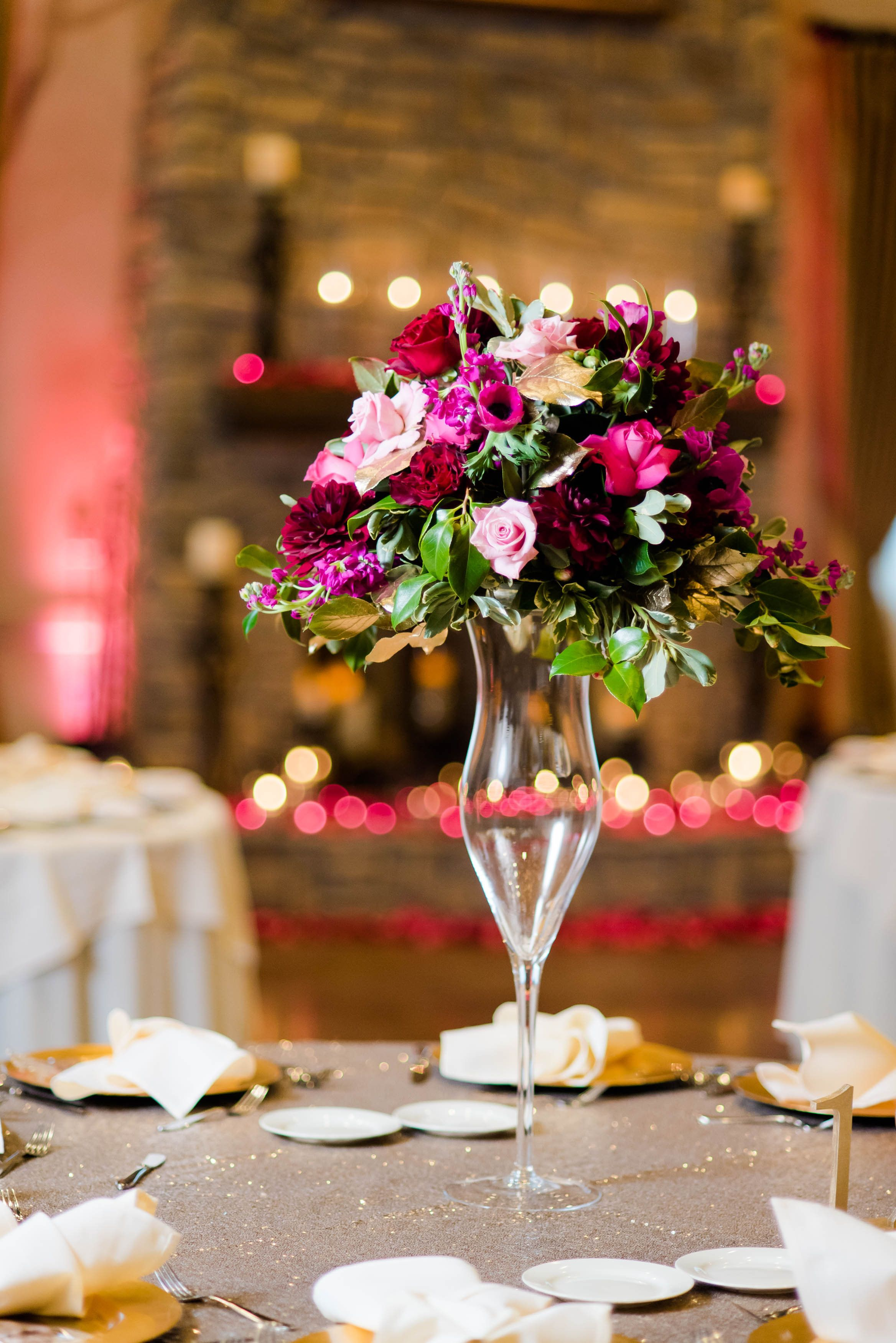 Tall centerpiece in fuchsia roses burgundy dahlias