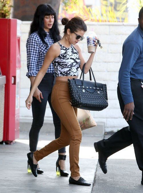 Selena Gomez wearing Chanel Black Leather CC Loafers Versace Signature Studded Handbag American Apparel Easy Jeans in Camel American Apparel Its called the Cat Fancy Print Cotton Spandex Sleeveless Crop Top