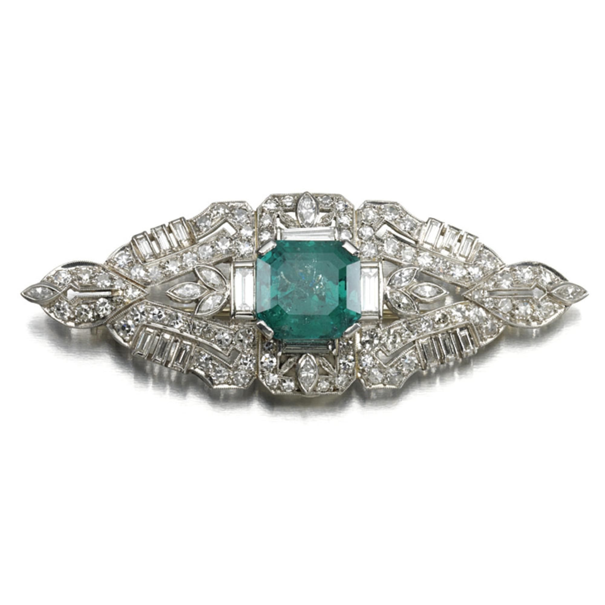 Emerald and diamond brooch, circa 1940. Set at the centre with an octagonal step-cut emerald within an open work floral motif set with single-cut, marquise-shaped and baguette diamonds, mounted in platinum.