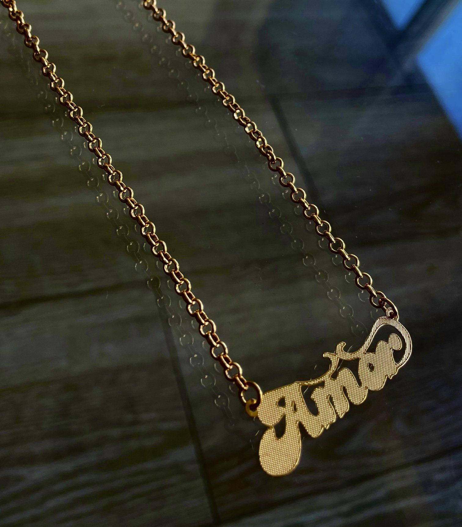 """An ode to a classic while feeling the love in this Amor Nameplate necklace! Amor - the Spanish word for Love, get all in your feelings with this cute golden tone, polished finish necklace. The perfect base for any Iridescent NYC layered look. Gold layered nameplate necklace. Thick round link chain, 17"""" long 1.75"""" plate"""