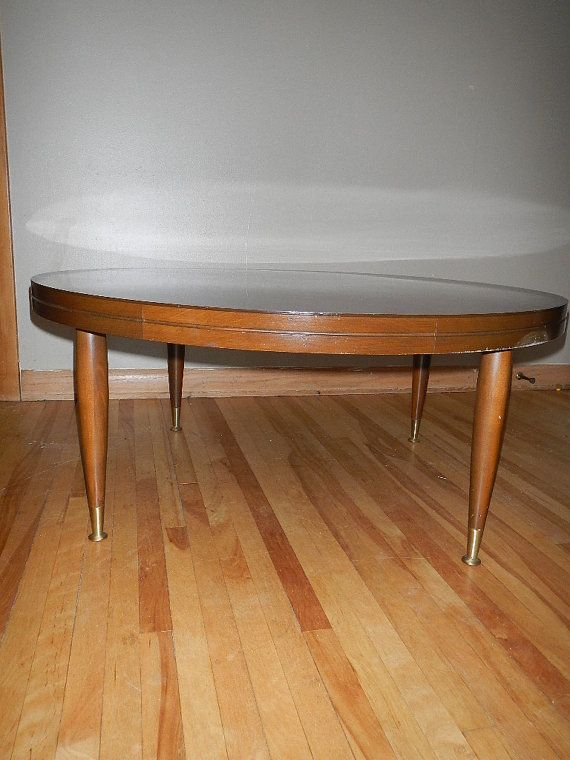 This is a vintage coffee table It has a faux wood formica top