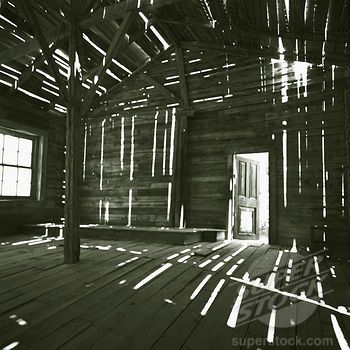 The interior of an old, empty, ruined wooden barn with sunlight streaming through wooden beams, painting the room in strips of light (4259-15098 / Z381_027 © Millennium Images)