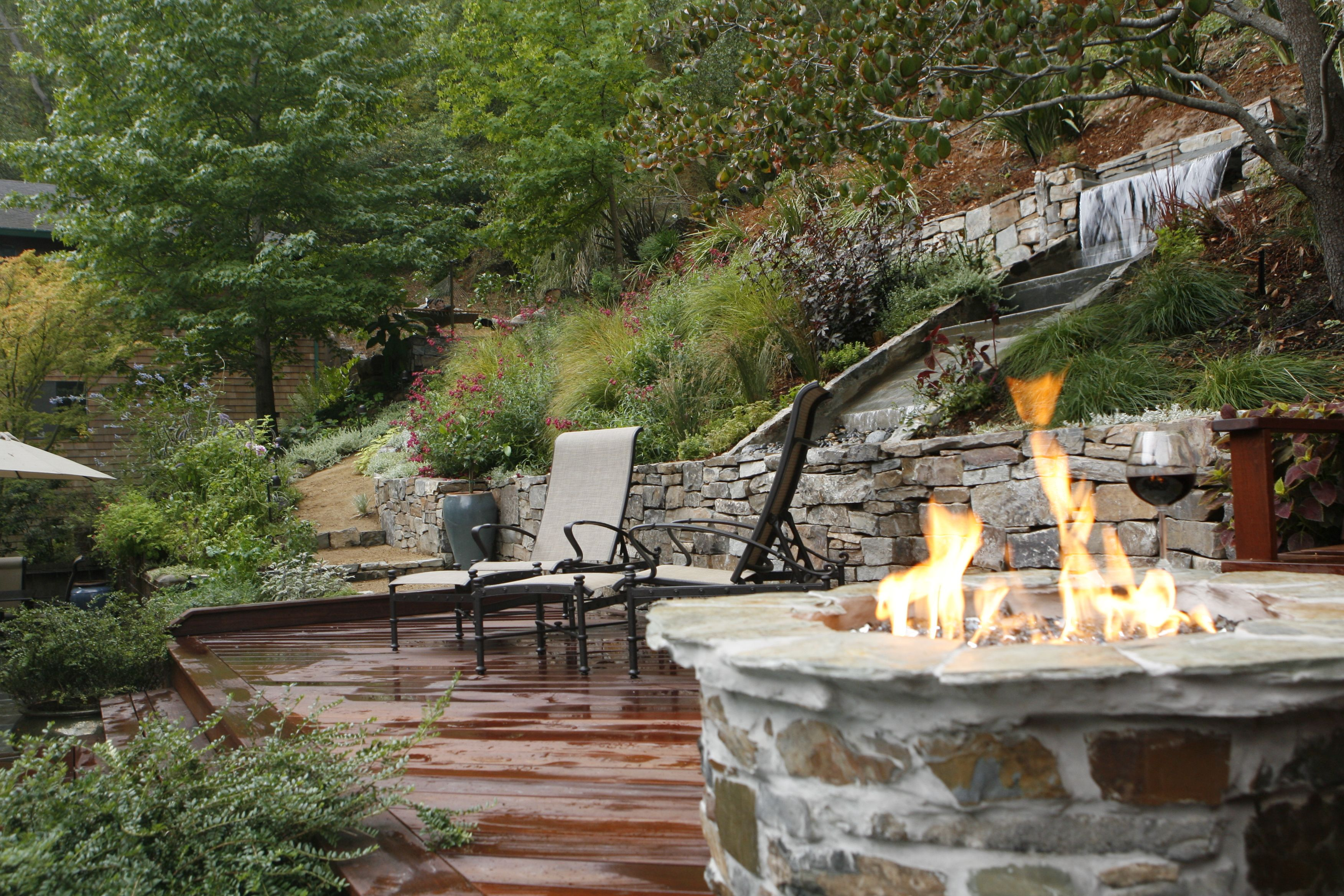 Tranquil Back Garden Slope With Fire Pit And Waterfalland Red Wine