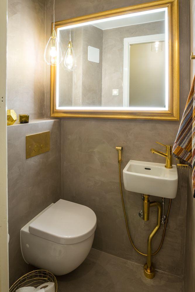 Suunnittelemani pieni wc, jossa mikrosementti ja messinki kohtaavat. Iso peili tekee pienestä tilasta valoisan ja avaran.