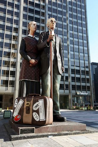 """God Bless America"" Sculpture by J. Seward Johnson, Jr. - depiction of Grant Wood's ""American Gothic"" Some people think the suitcase points to American jobs being lost overseas. The stickers on the suitcase are from Taiwan, Shanghai, China, Bangladesh, India and Thailand."