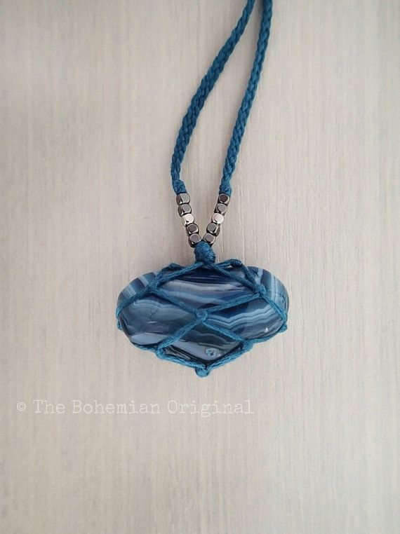 Beautiful ringed Blue Agate gemstone woven into a soft cotton macrame pouch. Accented with silver and gunmetal cube beads, this…