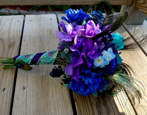 Peacock bridal bouquet, teal, purple, blue bridal bouquet with peacock feather accent #bridalbouquetpurple This beautiful bridal bouquet was inspired by natural peacock feather colors. Teal, king blue, purple flowers along natural peacock feathers make this piece one of a kind.  The handle has been wrapped with eggplant purple satin and peacock theme ribbons. Customize the handle color to match your wedding color. Measures 12 in length x 9 in diameter (feathers are not included in measurements #bridalbouquetpurple